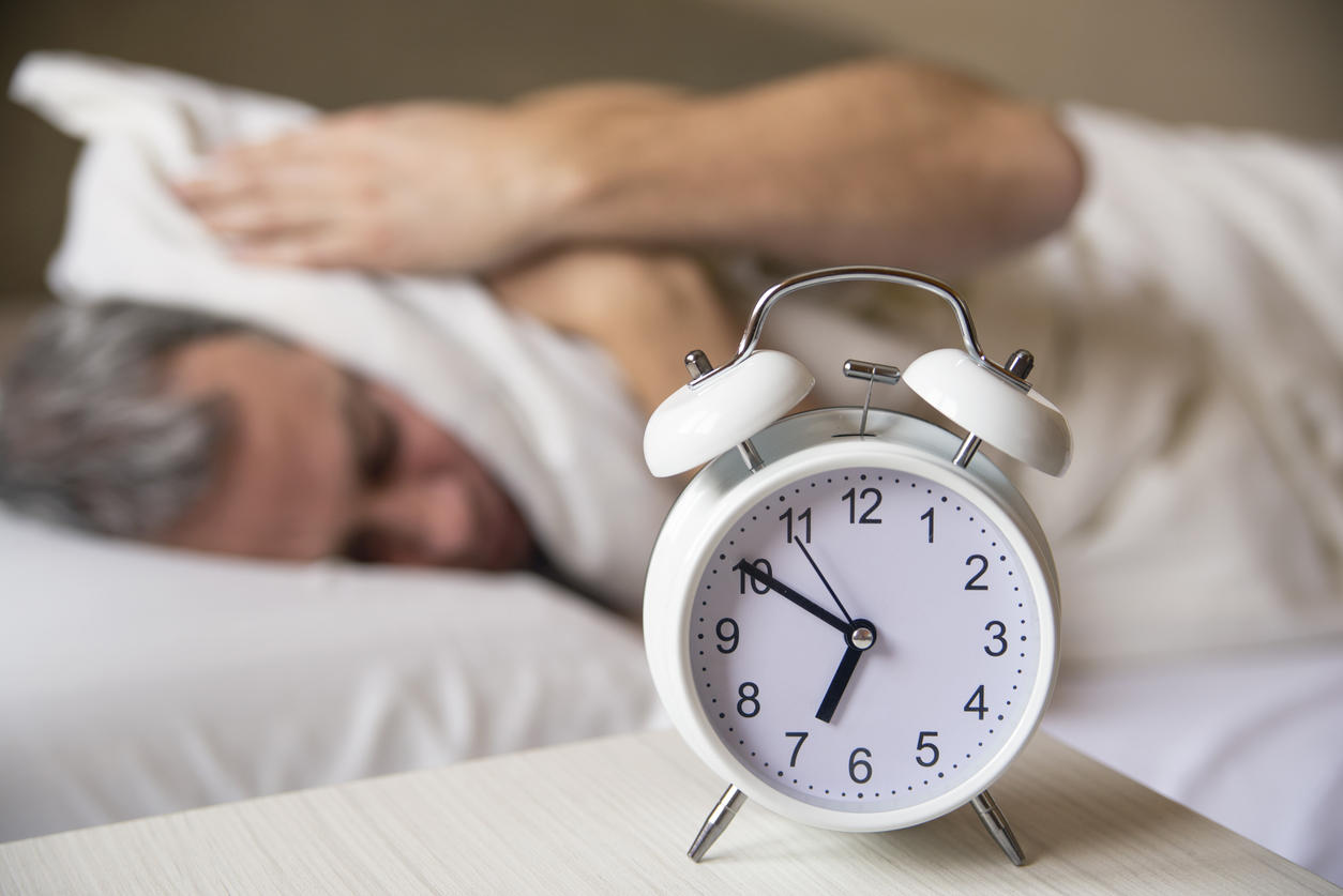 Sleeping Man Disturbed By Alarm Clock Early Morning. Sleepy Young Man Covering Ears With Pillow As He Looks At Alarm Clock In Bed